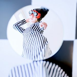 Reflection of woman in striped dress with orange sunglasses